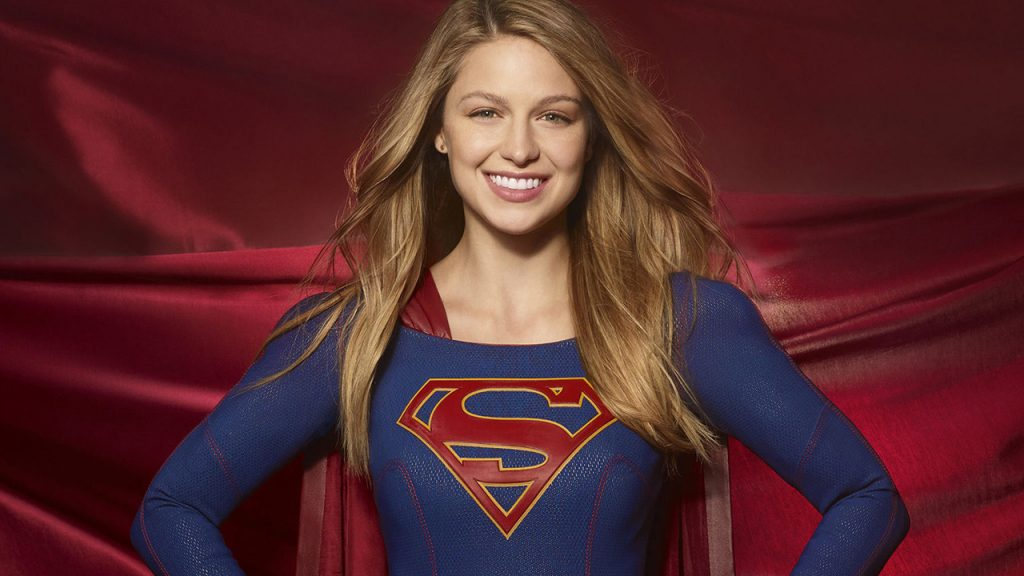 Promo image for Supergirl showing supergirl posing in from of a red background