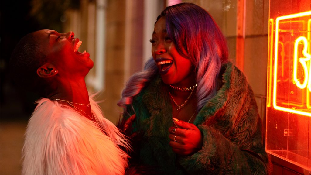 Still from Been So Long showing two friends laughing next to a window with a neon sign