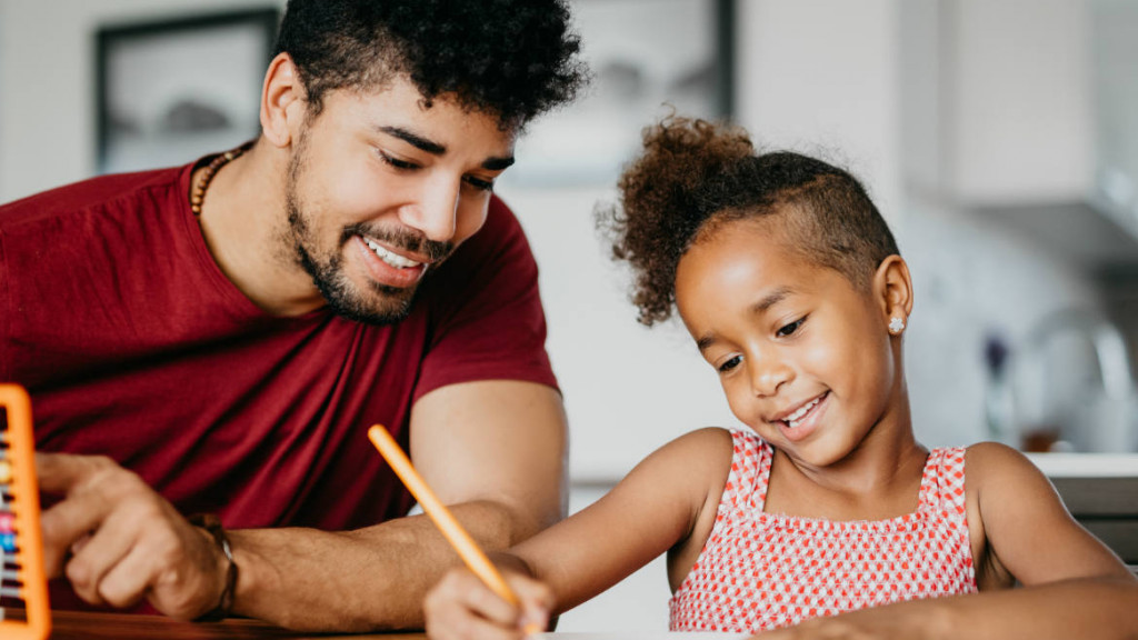 Dad smiling beside his daughter helping her with homework.