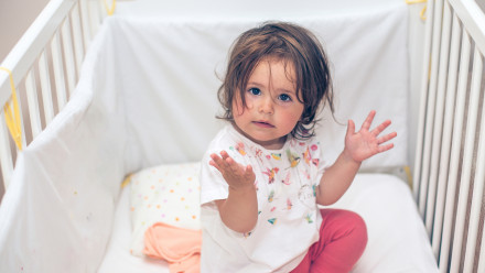 baby sitting in a crib with her hands up and a fed up look on her face