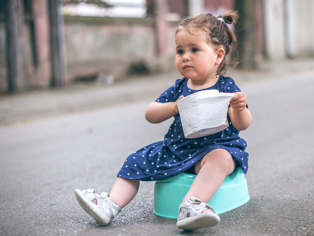 toddler girl sitting on a potty on the street holding toilet paper