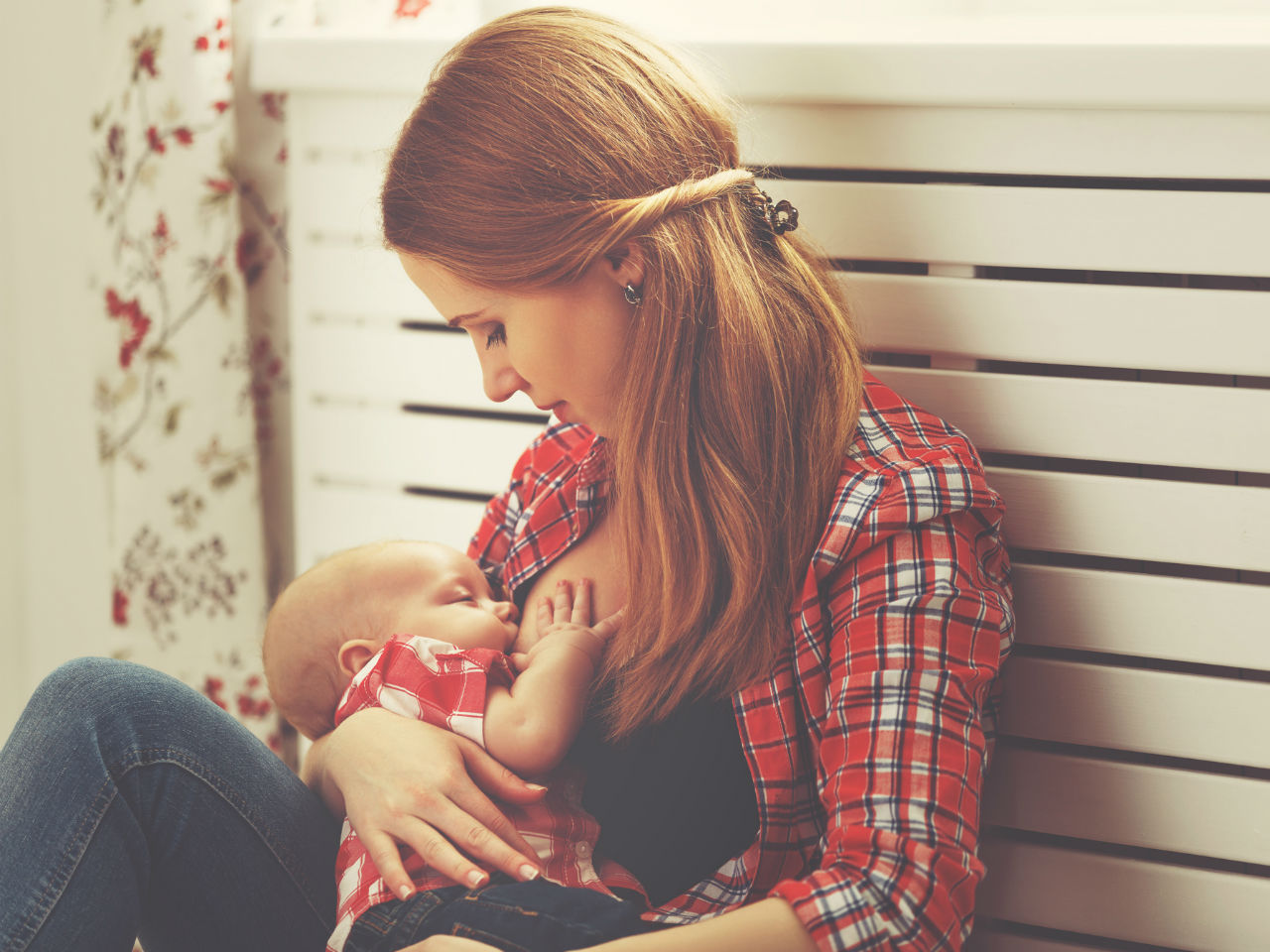 Young mom breastfeeding her baby at home
