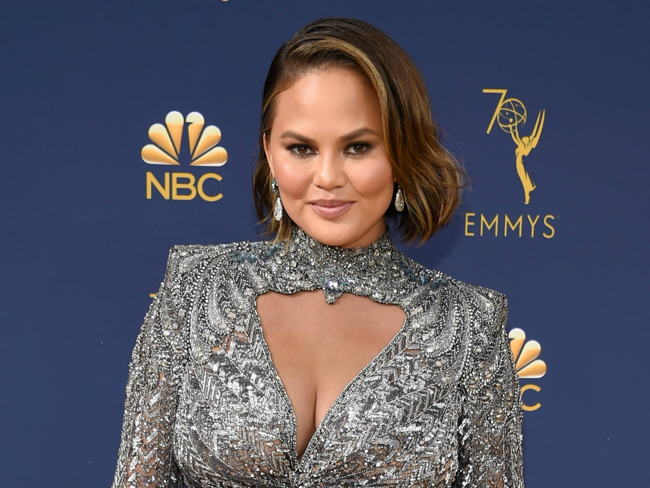 Chrissy Teigen smiling in a silver dress on the Emmys red carpet