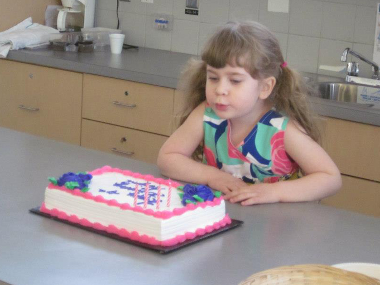A little girl with pigtails blowing out her birthday cake