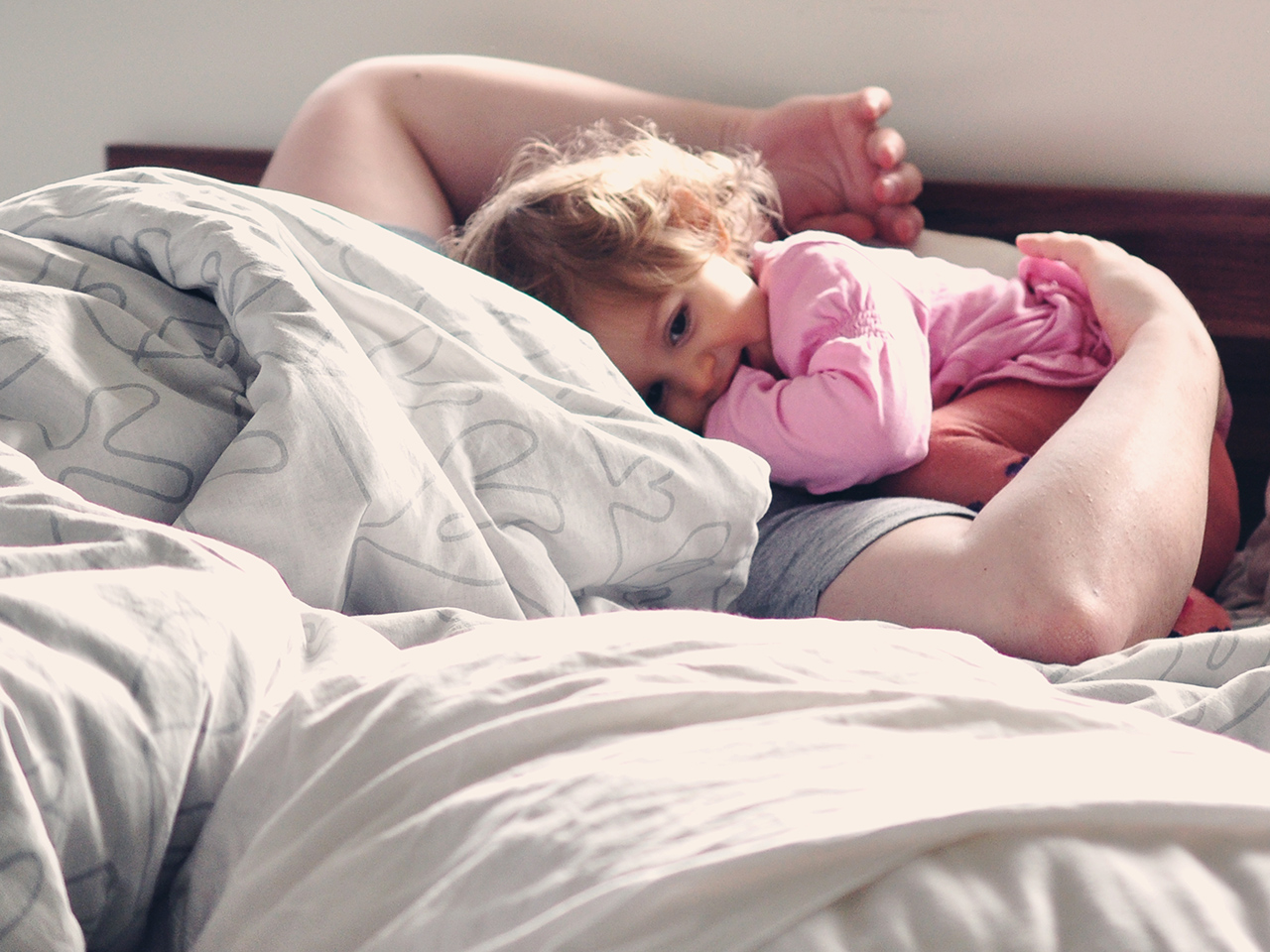 A toddler girl waking her dad up in bed