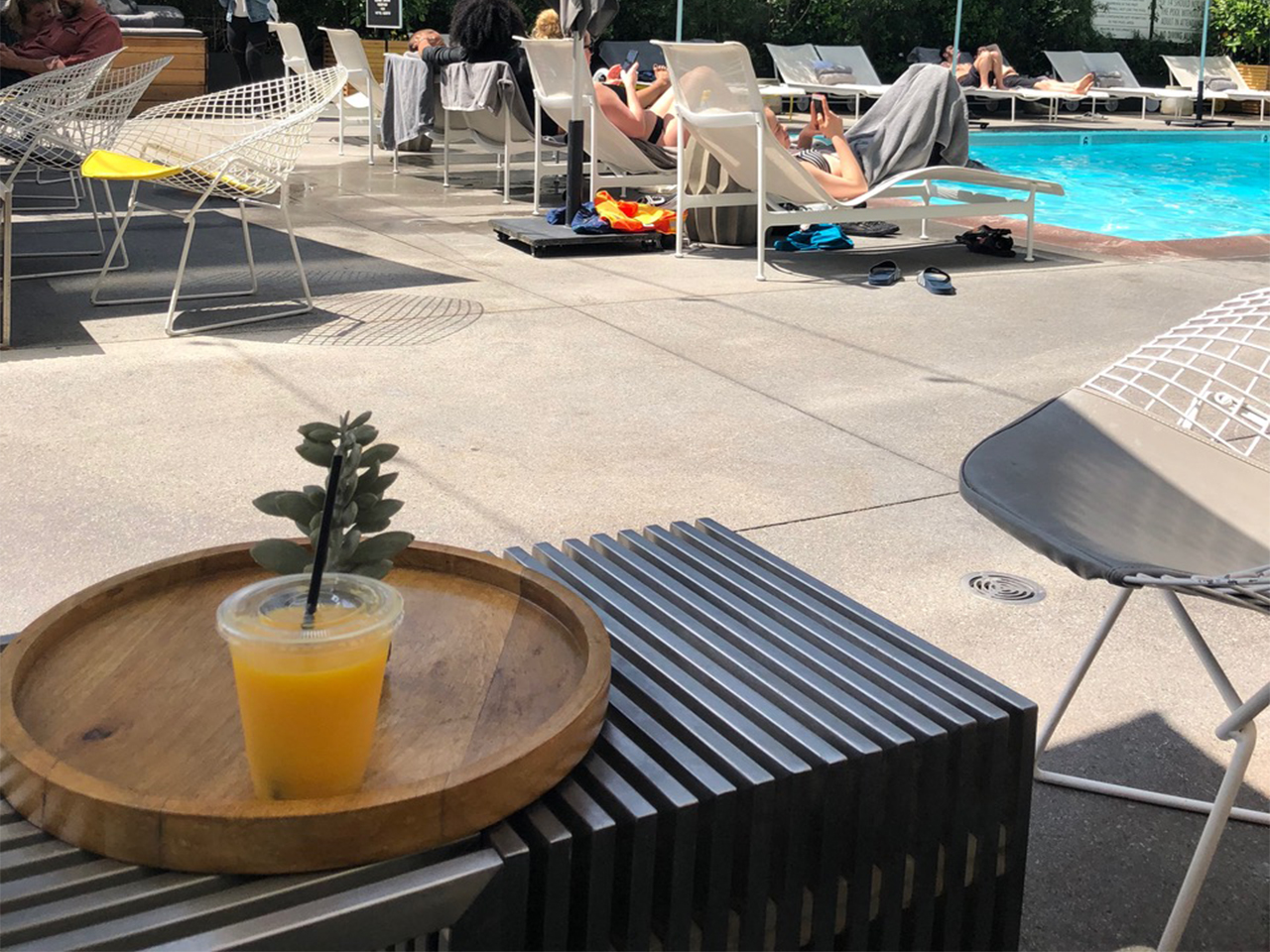 orange cocktail on a table near a pool