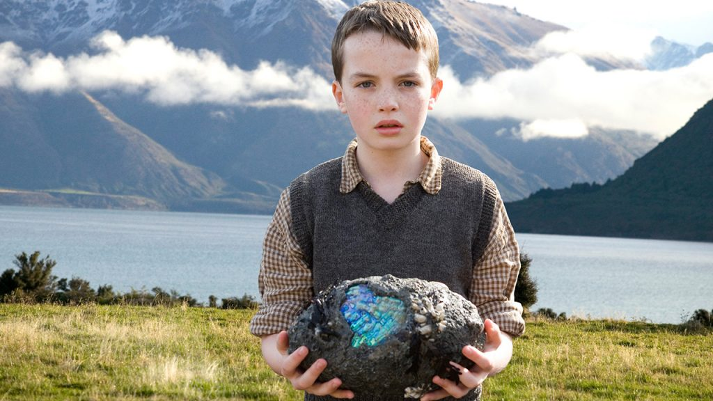 Promo image from The Water Horse Legend of the Deep showing a boy in the mountains near a lake holding a magic egg