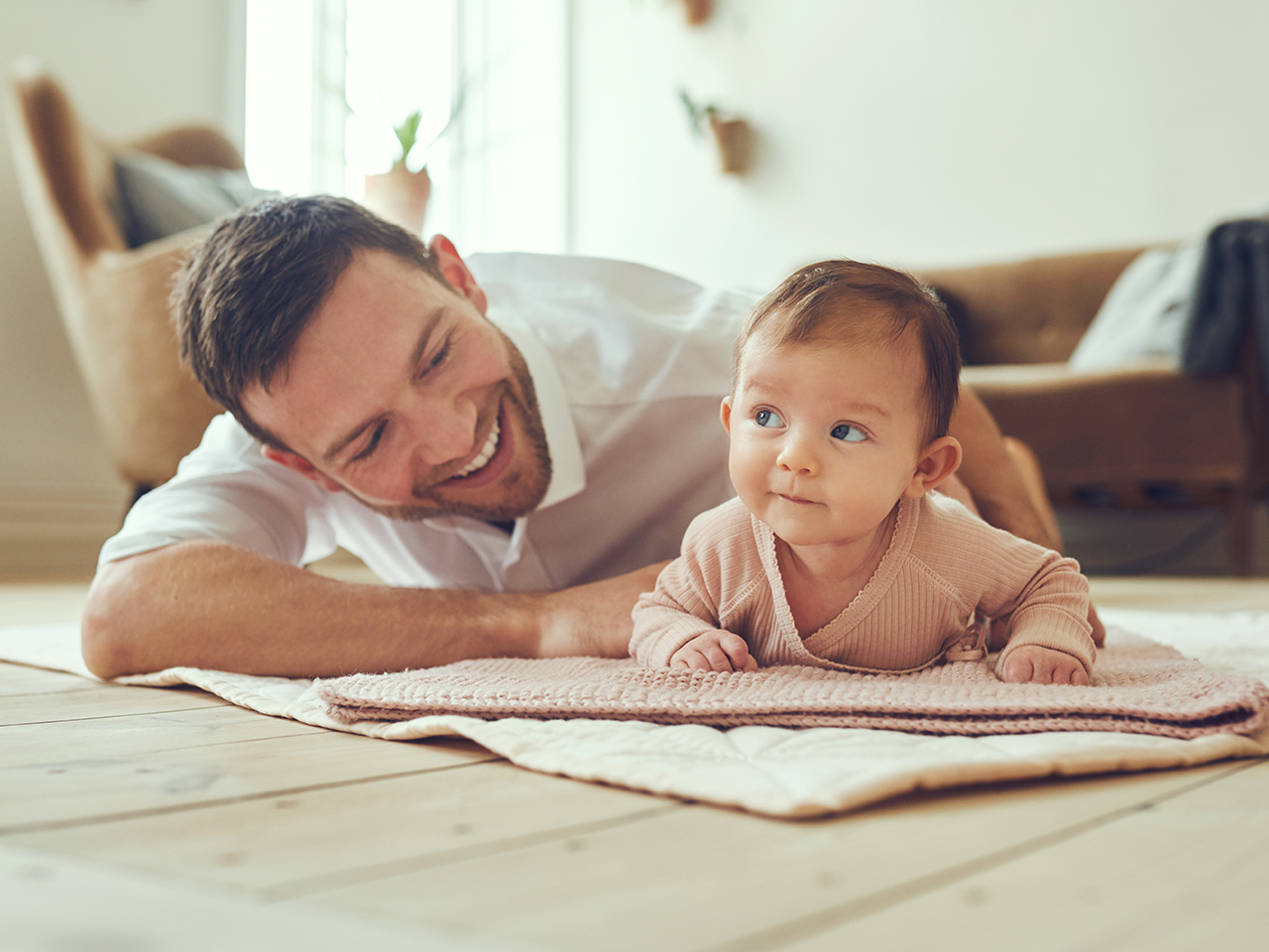 A dad smiling at his daughter who is doing tummy time