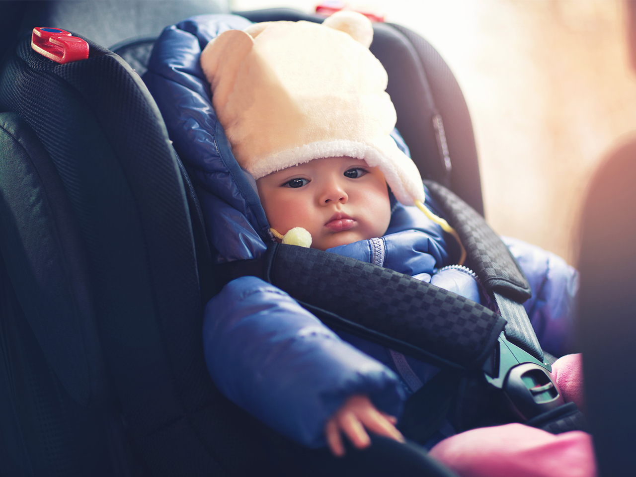 Baby sitting in a carseat with coat on