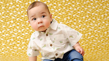 9 month old baby sitting down against yellow background