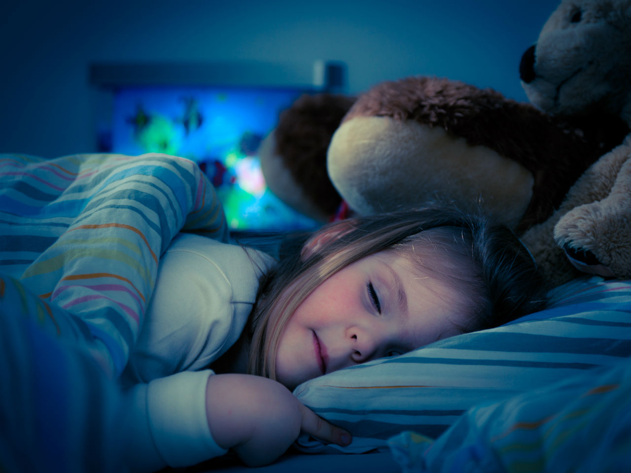 Little girl sleeping in bed with a stuffed animal