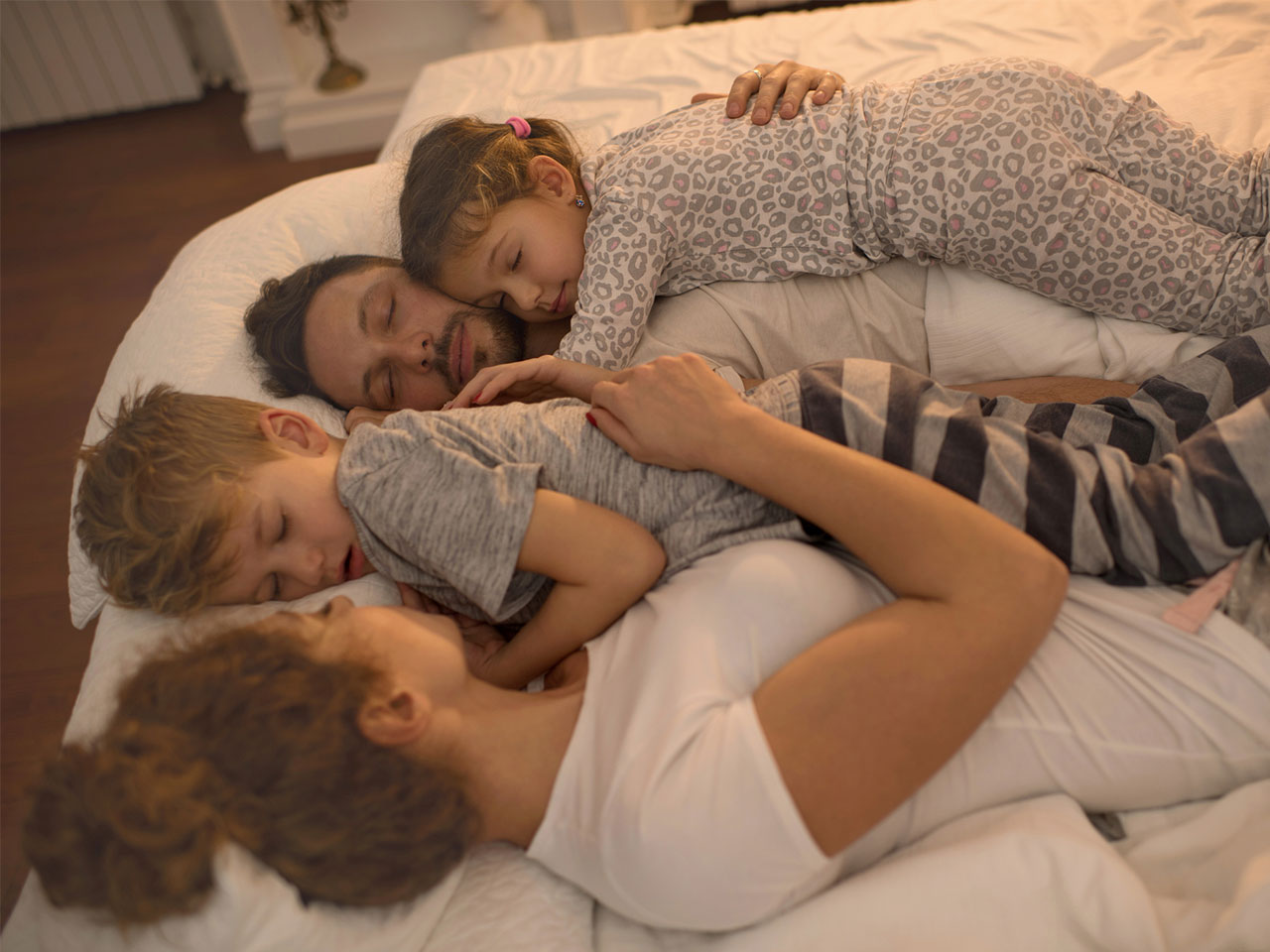 Young family sleeping next to one another on a bed