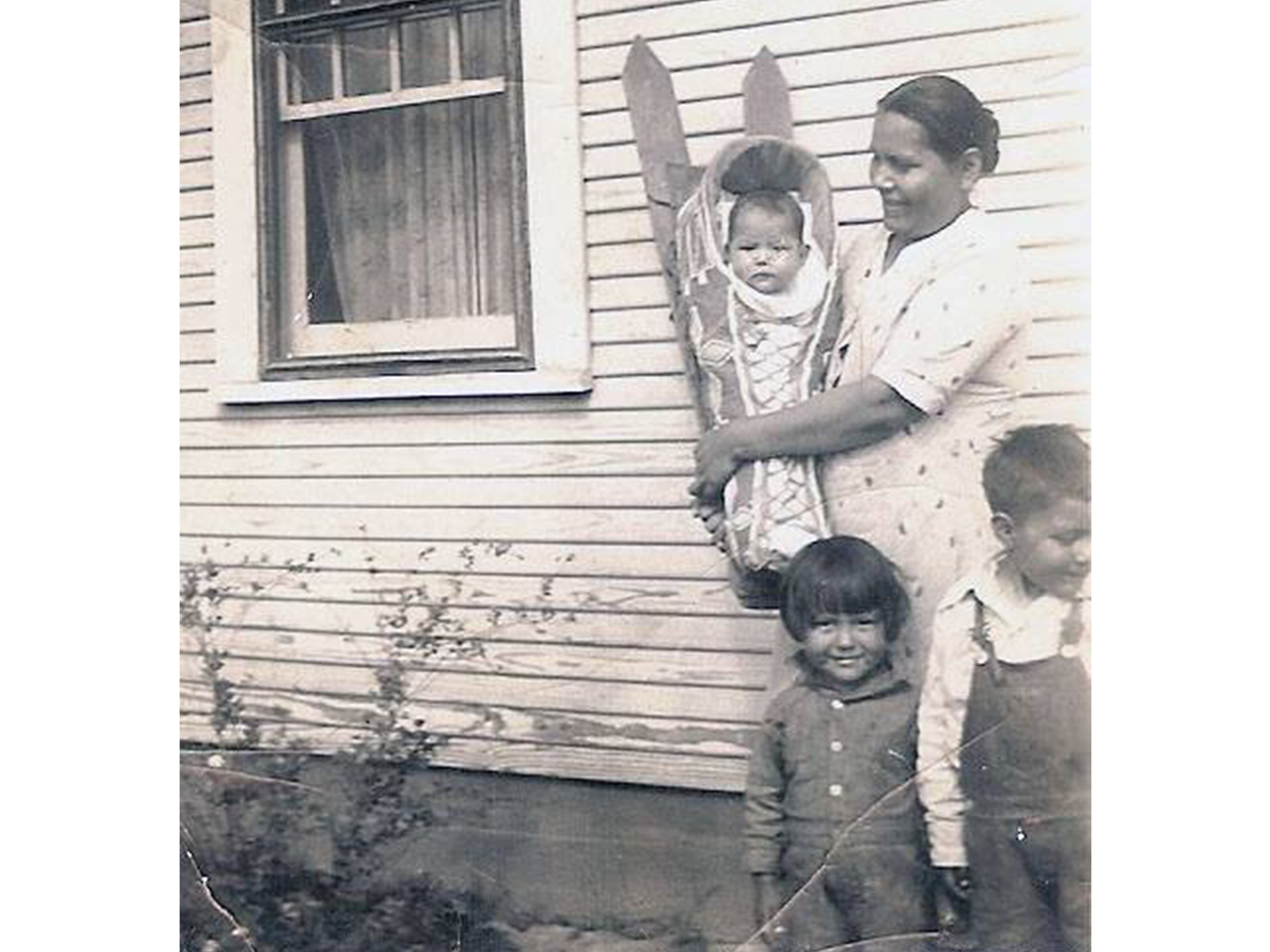 A black and white photo of a family smiling outside a house, with the baby wrapped in a cardleboard