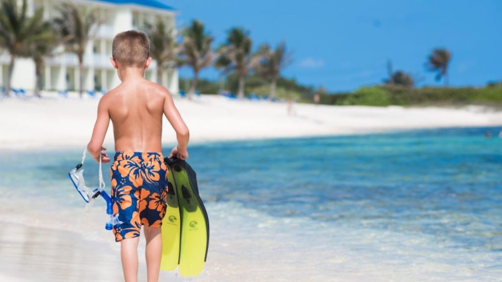 boy walking along beach with flippers