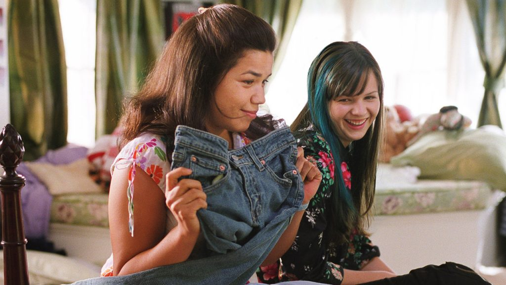 Promo image for sisterhood of the travelling pants showing two young women in a bedroom laughing about a pair of jeans