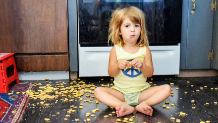 little girl sitting on the floor surrounded by crackers