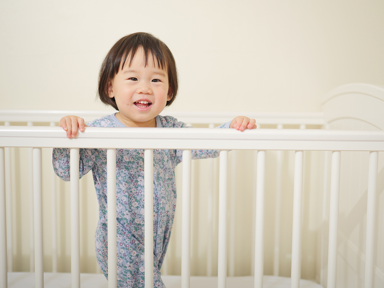 12-month-old baby in floral pyjamas standing up in a white crib