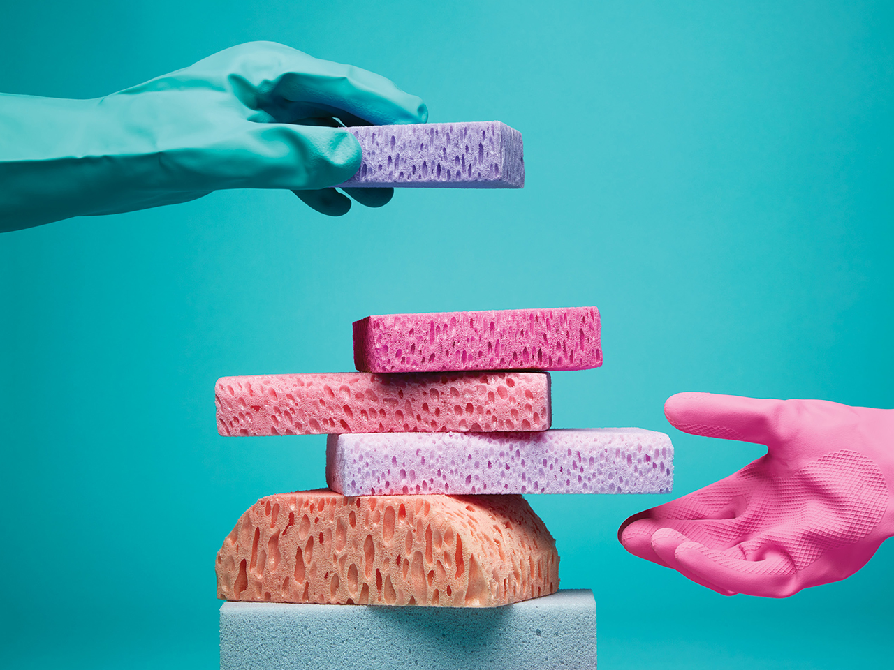 A blue dishwashing glove places a purple sponge on top of a stack of various pink sponges. A pink dishwashing glove is hovering near the bottom of the sponge tower.