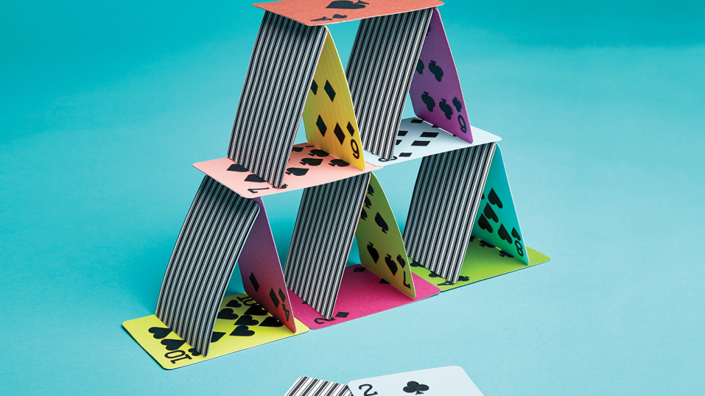 Striped and multicoloured playing cards formed into a house of cards. Two cards lie at the bottom near the formation.