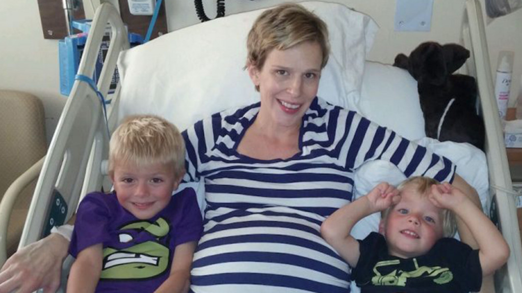 Jillian Bickmore lays in a hospital bed with her two sons on either side of her pregnant belly.