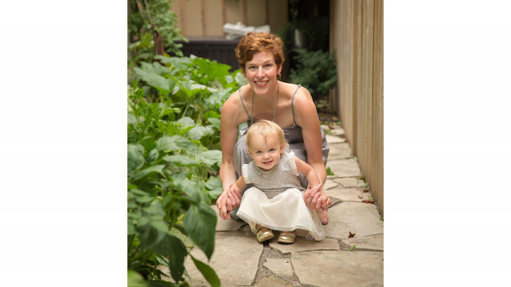 Jillian Bickmore posing with her daughter outside next to some greenery.