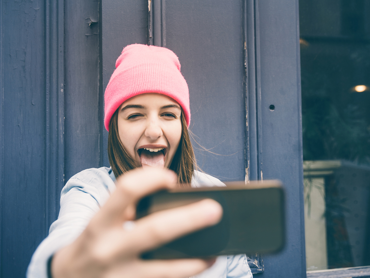 teen girl in a pink knit hat holds her phone out in front of her to take a selfie.