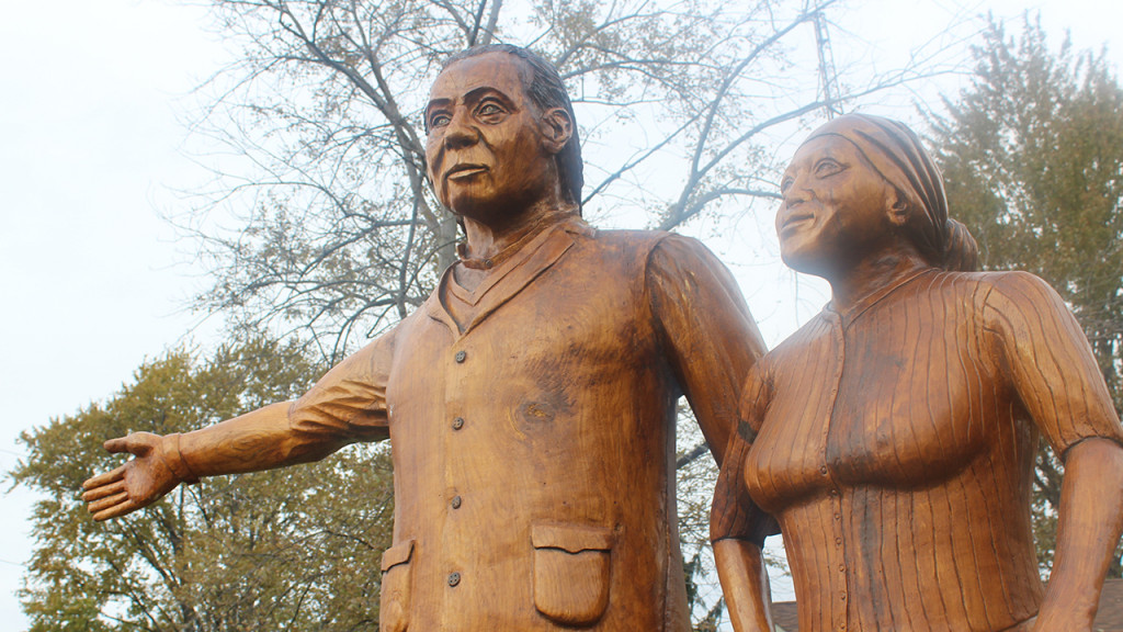 three wooden statues of a man, a woman, and her child near the buxton historic site and museum.