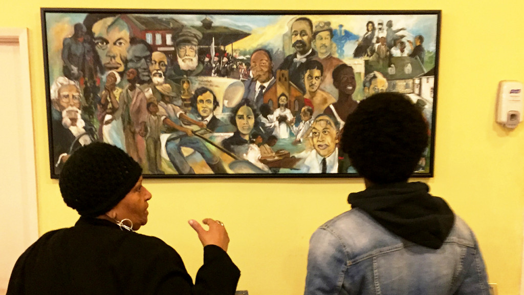 an older black woman and a younger black woman stand in front of a painting that celebrates historic black figures.