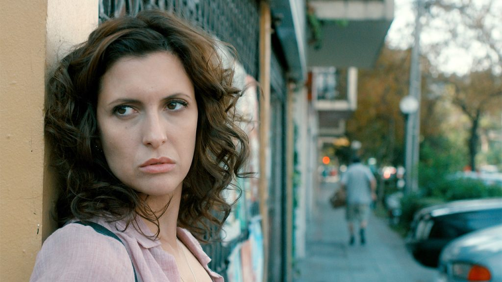 Promo image for Dry Martina showing a woman standing on a street corner