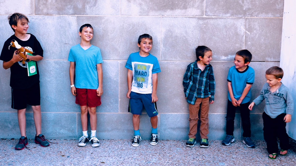six boys standing against a wall