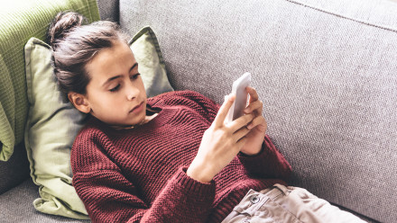 Girl laying on the couch on her smartphone