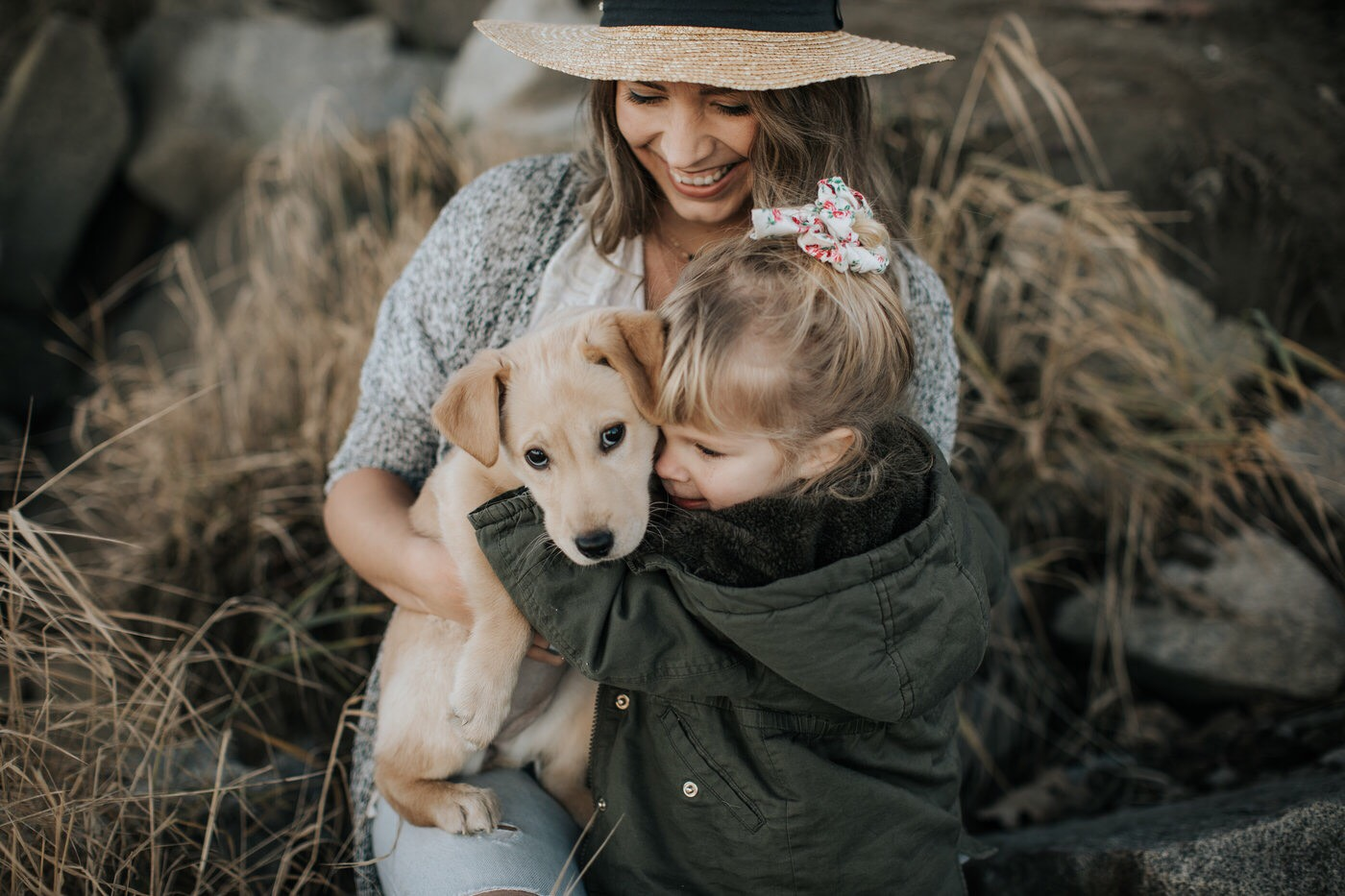 Mother and daughter hug family dog by the water