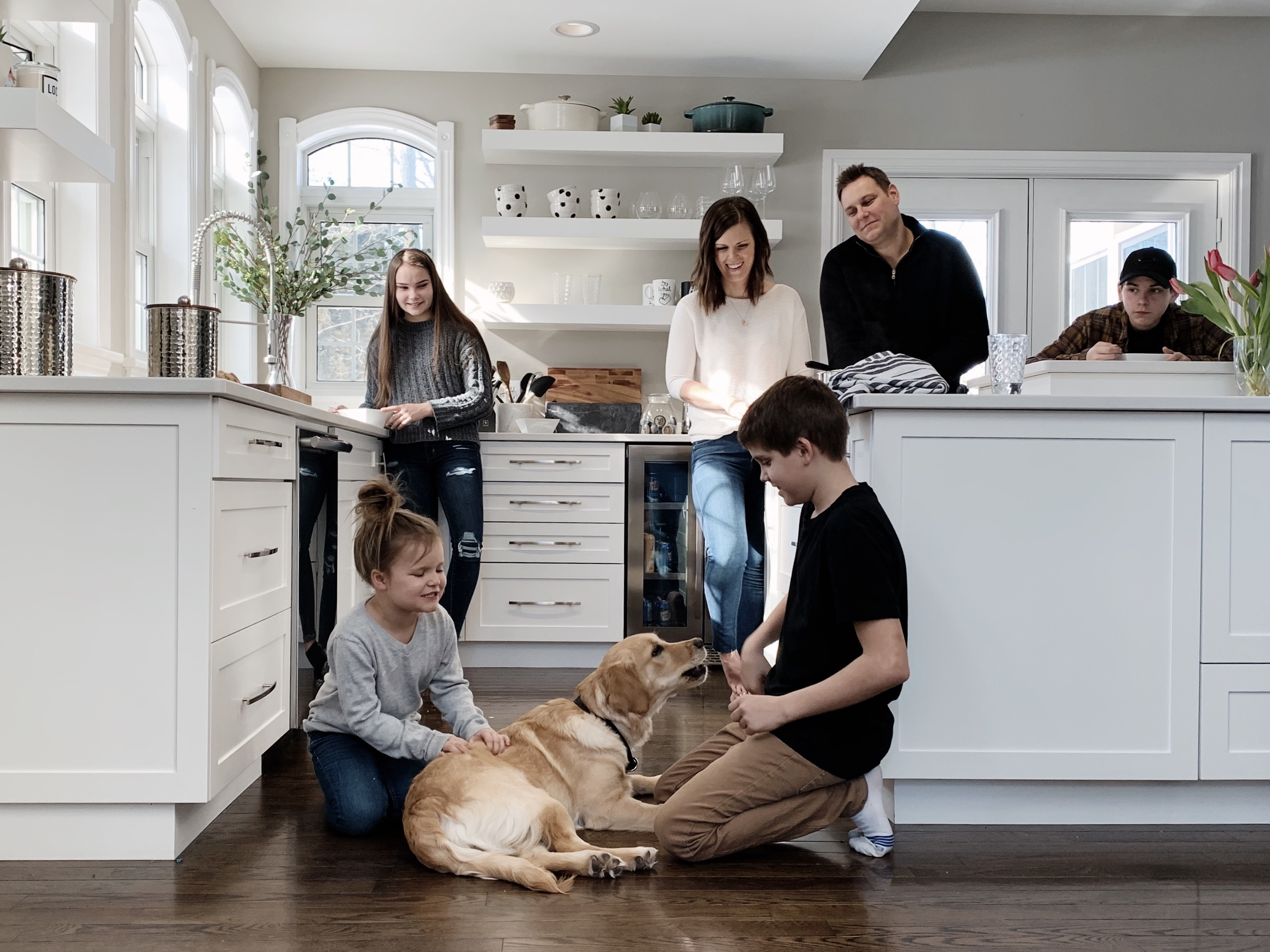 Mom and dad with kids and family dog in kitchen