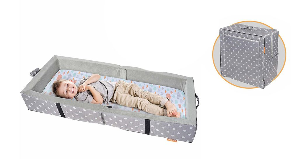 Little boy laying in a portable bed