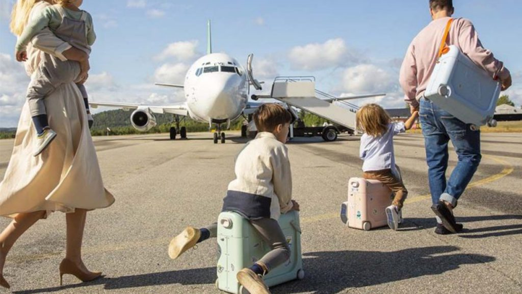 Mother, father, son and daughter carry/roll across the airpot runway on/with their portable bed box