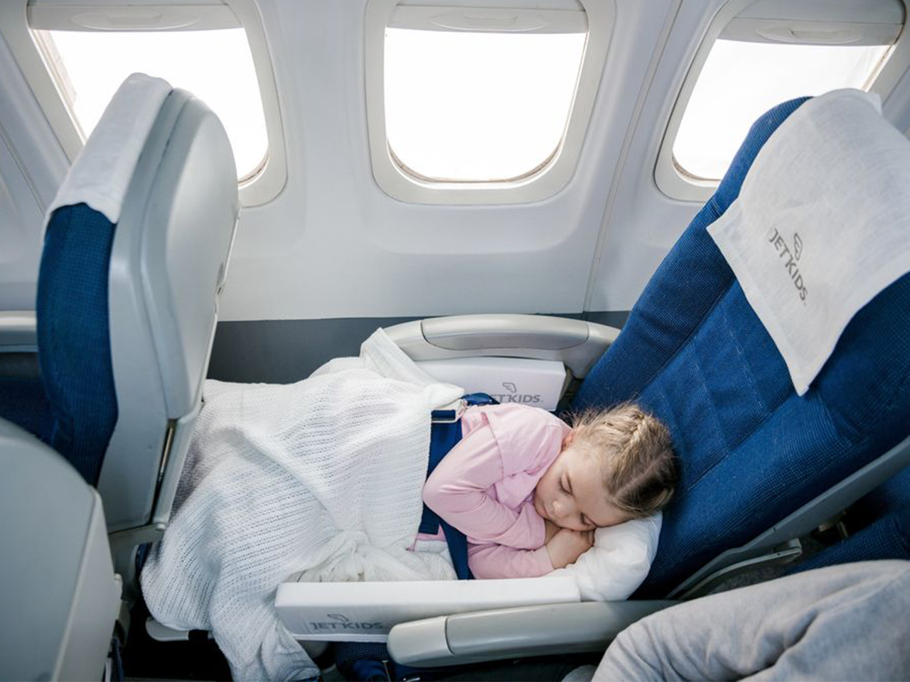 Little girl sleeping comfortably on a plane
