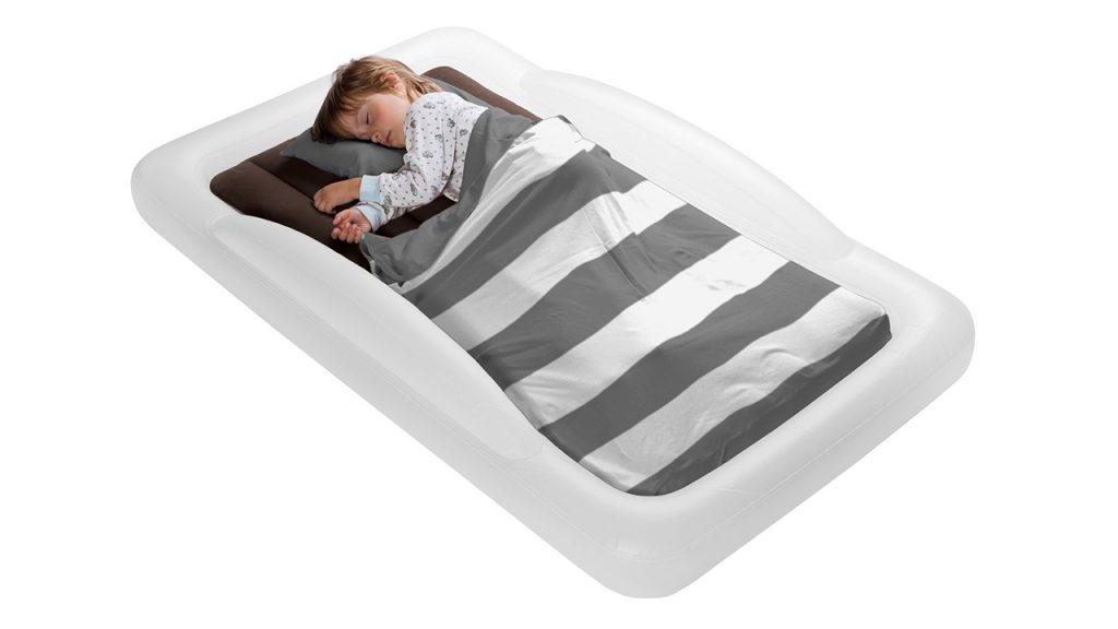 A little boy sleeping on an inflatable grey and white bed