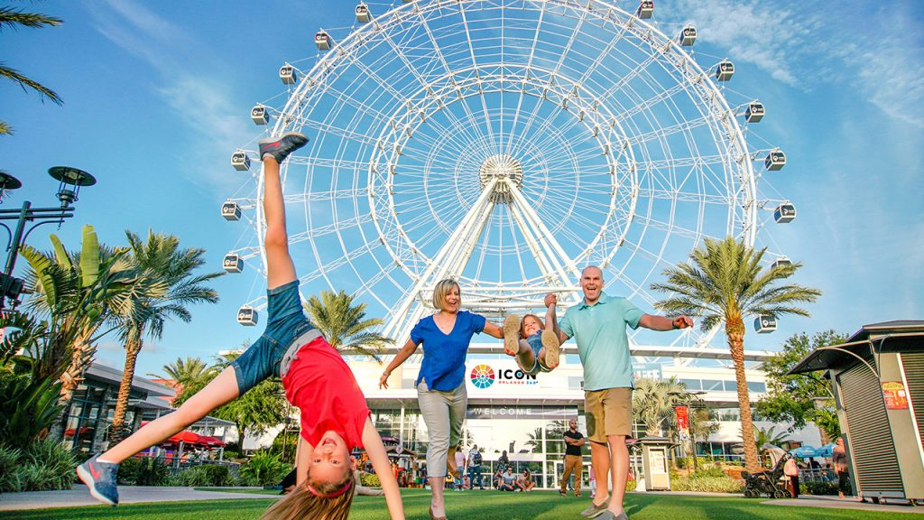 Photo of family playing in front of the ICON Orlando observation wheel