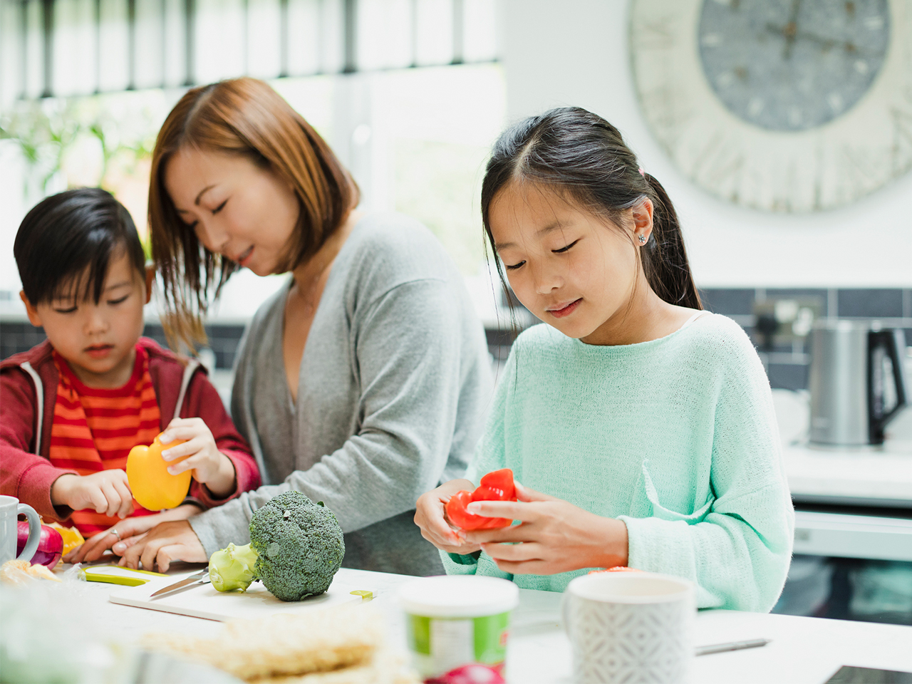 Mom and two kids prepping veggies in a kitchen