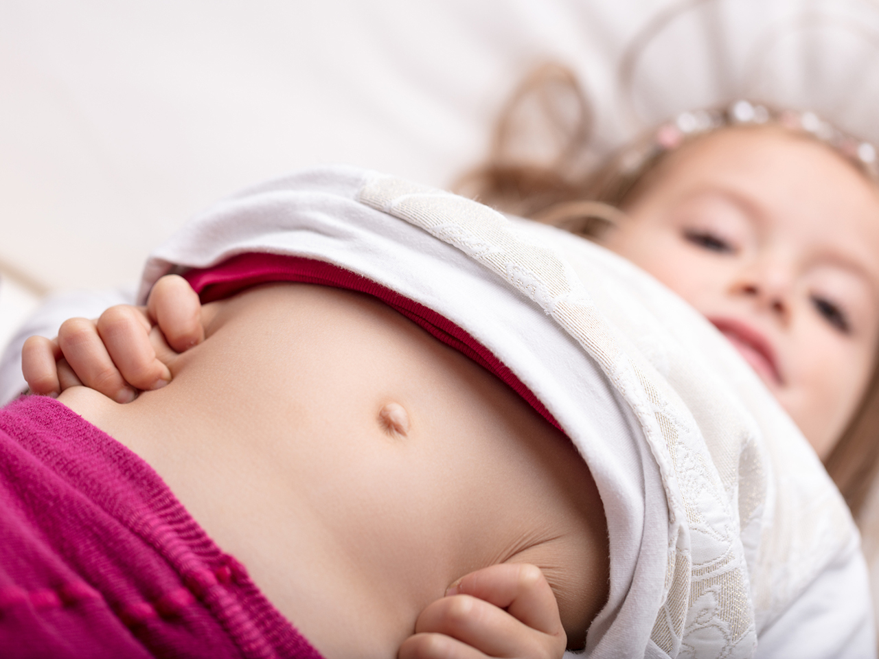 Little girl pushing out her belly while she squeezes her sides