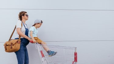 pregnant mom in overalls pushing her son in a cart