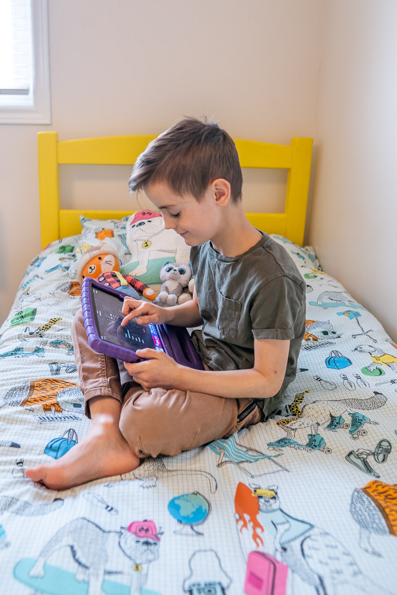 Christine's son setting an alarm on his iPad, sitting on his bed