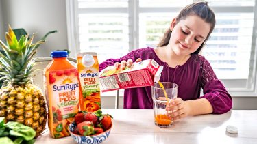 Christine's daughter pouring SunRype Fruit Plus Veggies juice into a glass