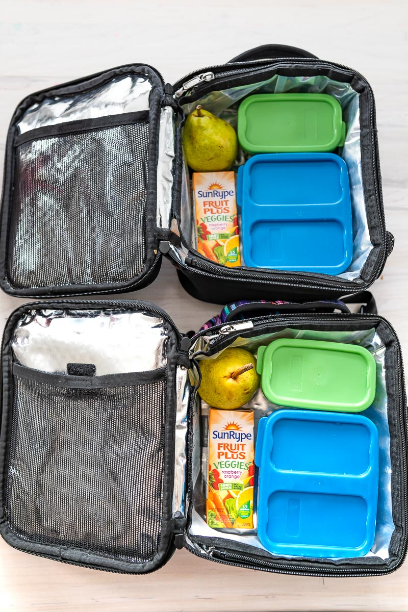 Two packed lunch boxes with containers, fruit, and SunRype Fruit Plus Veggies juice boxes