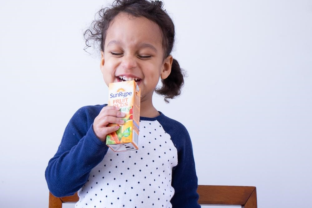Photo of Marielle's daughter smiling and drinking a SunRype Fruit Plus Veggies juice box