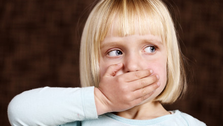 blond little girl covering her mouth