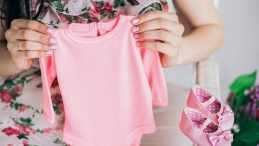 New mom holds up pink baby clothes
