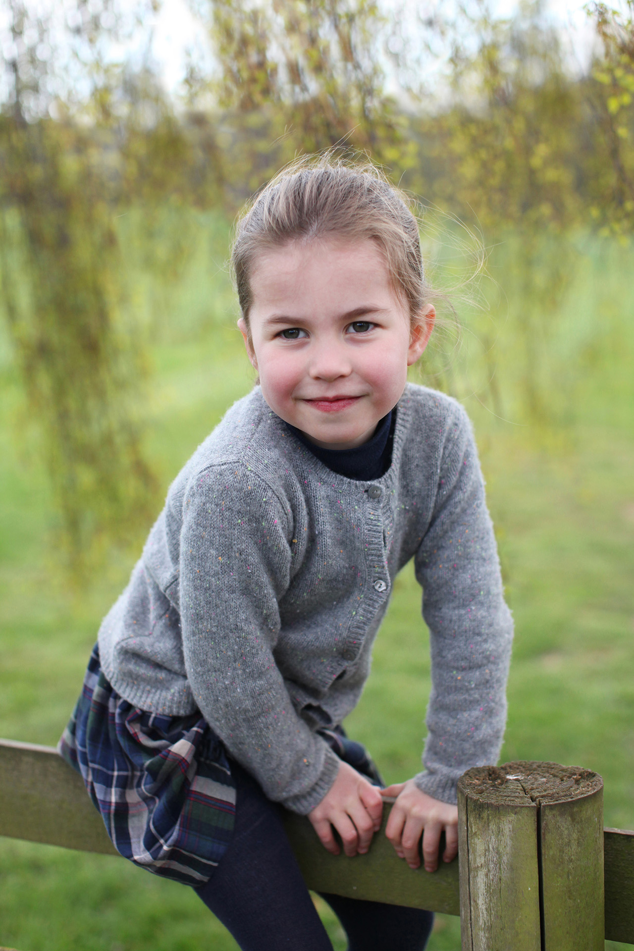 princess charlotte sitting on a fence in the country