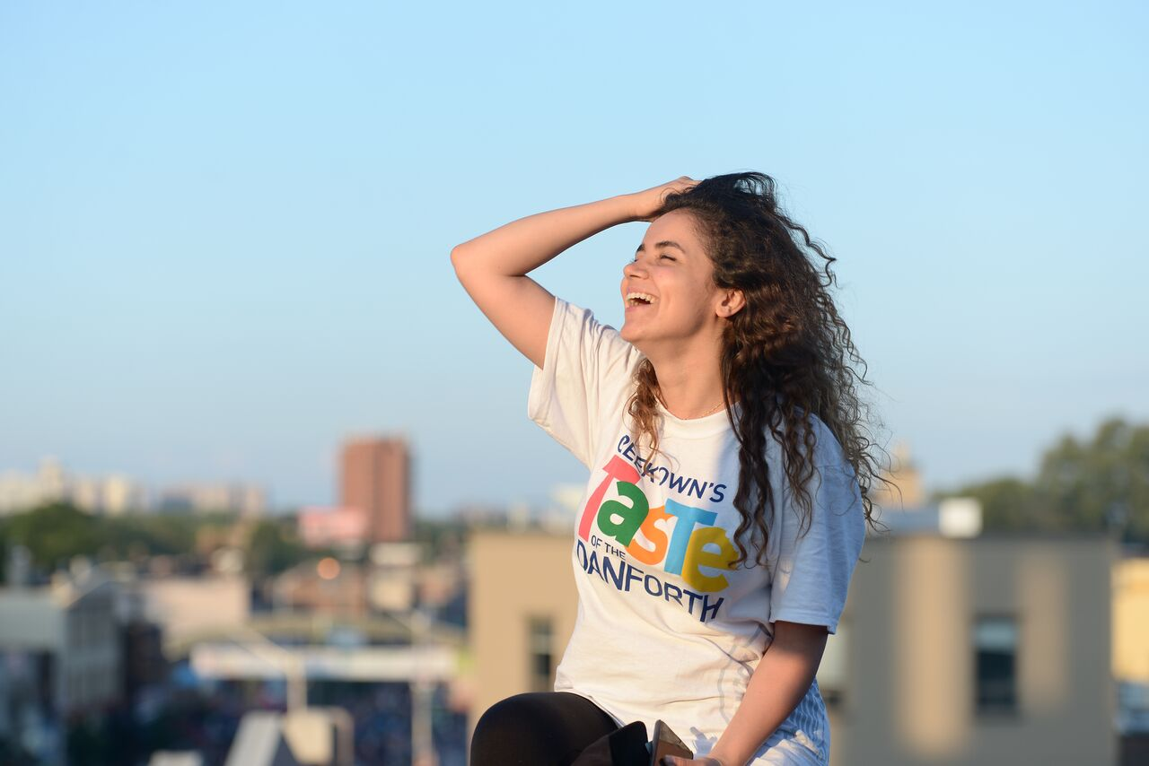 Girl smiling in the sun wearing a Taste of the Danforth t-shirt