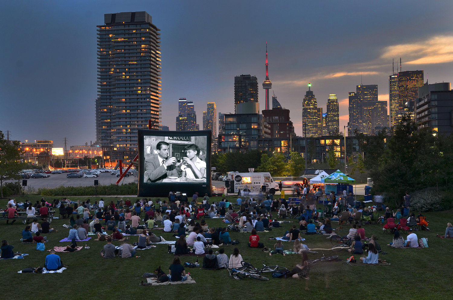 Toronto Outdoor Picture show playing a black and white movie on the grass beyond the Toronto skyline